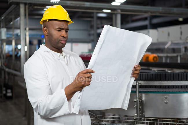 Серьезный работник мужского пола, читающий инструкции на соковом заводе — стоковое фото