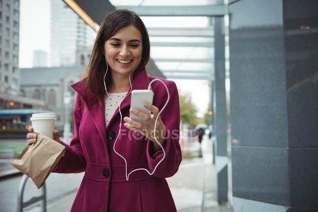 Бізнес-леді проведення чашки одноразові кави і посилки під час прослуховування музики поблизу Офісна будівля — стокове фото
