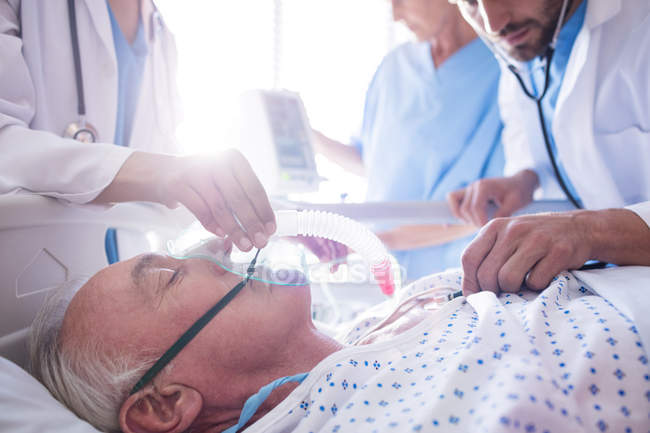Team of doctors putting oxygen mask on a male senior patient face in the hospital — Stock Photo