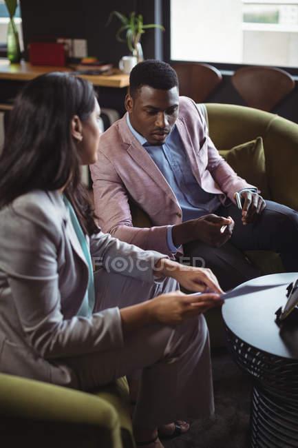 Homme d'affaires et un collègue discuter au document dans office — Photo de stock