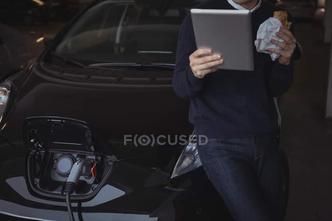 L'homme à l'aide de tablette numérique et grignoter tout en chargeant la voiture électrique dans garage — Photo de stock