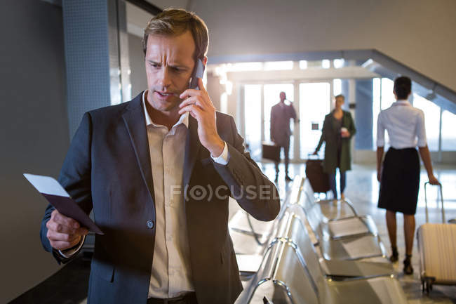 Businessman talking on phone while holding passport and boarding pass at airport terminal — Stock Photo