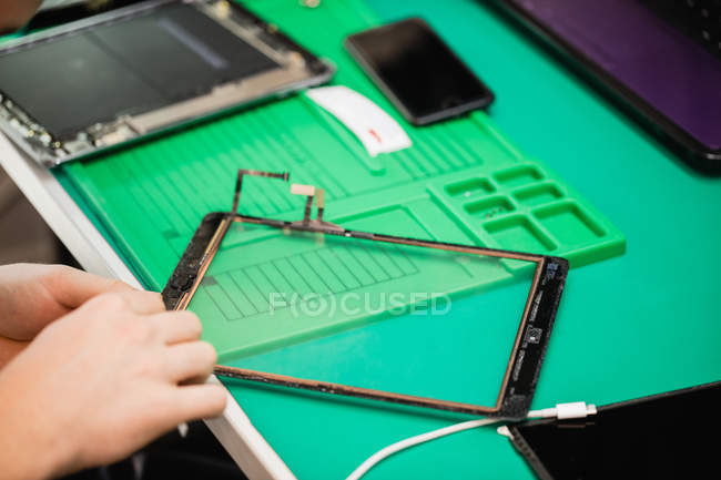 Close-up of man repairing digital tablet in repair centre — Stock Photo
