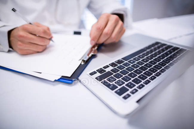 Mid section of doctor writing on clipboard in clinic — Stock Photo