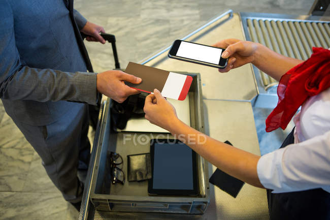 Funcionários de aeroporto feminino usando o celular para digitalizar o passaporte no terminal do Aeroporto — Fotografia de Stock