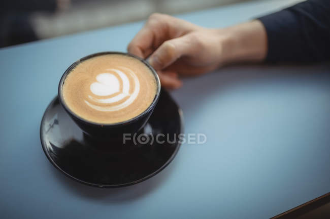 Hand of male executive holding coffee cup in cafeteria — Stock Photo
