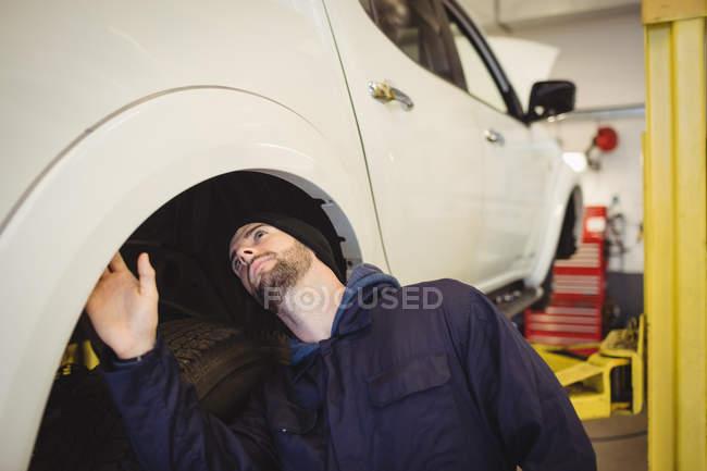 Meccanico esaminando un freno a disco ruota auto in garage di riparazione — Foto stock