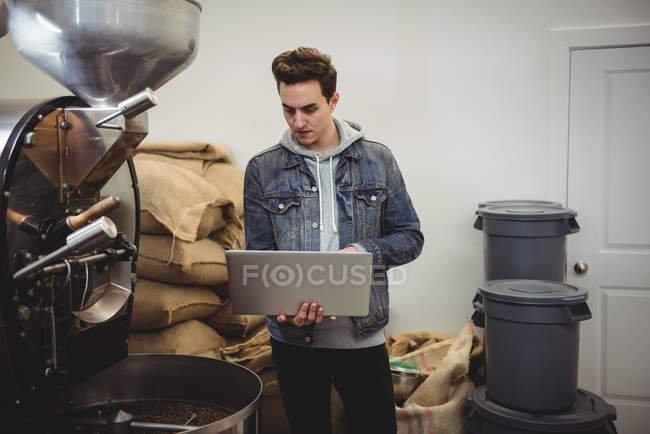 Man using laptop while standing besides coffee grinding machine in coffee shop — Stock Photo