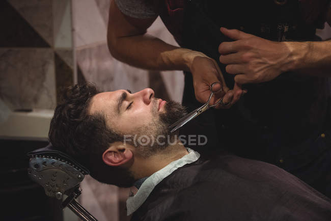 Customer getting beard trimmed with scissors in barber shop — Stock Photo