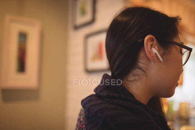 Woman listening to music with earphones at home — Stock Photo