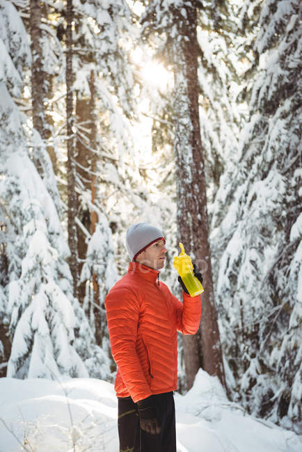Man drinking water from bottle in forest during winter — Stock Photo