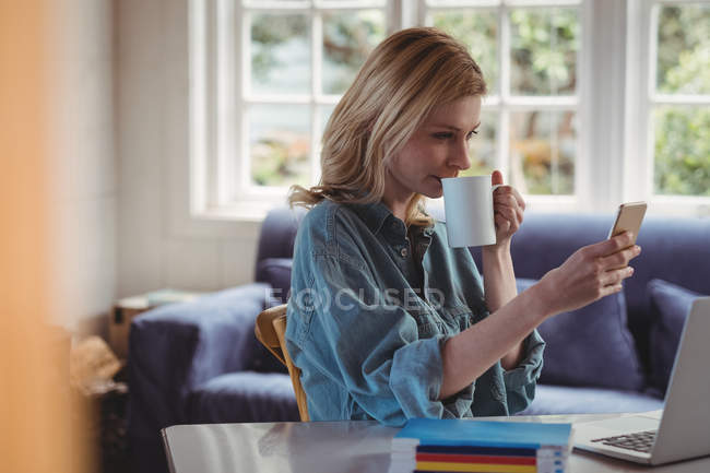 Belle femme utilisant un téléphone portable tout en prenant un café dans le salon à la maison — Photo de stock