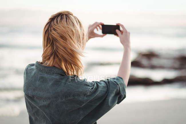 Rückansicht einer Frau, die am Strand Fotos mit dem Handy anklickt — Stockfoto