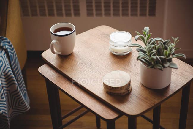 Teetasse, Untersetzer und Zimmerpflanze auf Holztisch im heimischen Wohnzimmer — Stockfoto