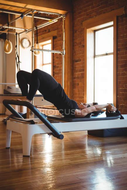 Женщина практикует пилатес на реформаторе в фитнес-студии — стоковое фото