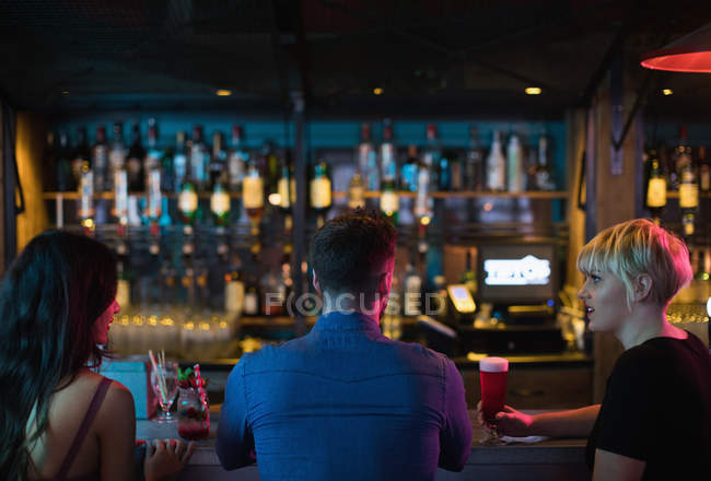 Friends enjoying alcoholic drinks at counter in bar — Stock Photo