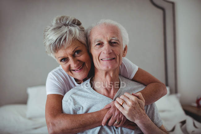 Portrait of senior woman embracing senior man on bed in bed room — Stock Photo