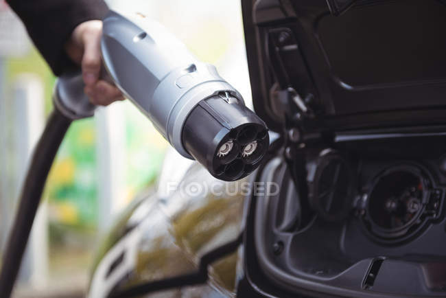 Close-up of male hand charging electric car at electric vehicle charging station — Stock Photo
