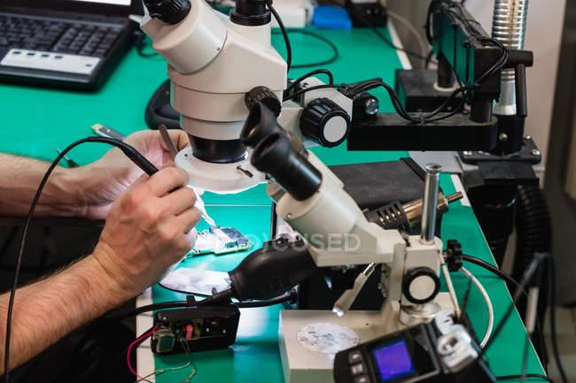 Mann repariert Handy in Reparaturzentrum — Stockfoto