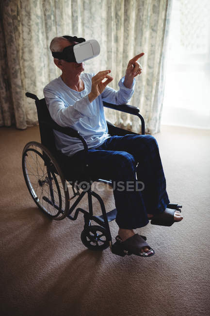 Senior man sitting on wheelchair and using virtual reality headset in bedroom at home — Stock Photo