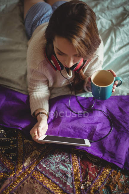 Beautiful woman using digital tablet while having coffee on bed at home — Stock Photo