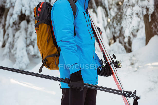 Mid section of skier walking with ski on snow covered mountains — Stock Photo