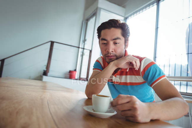 Thoughtful man sitting with cup of coffee on table in coffee shop — Stock Photo