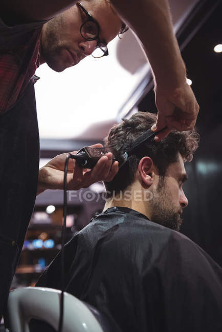 Male barber cutting client hair with trimmer in barbershop — Stock Photo