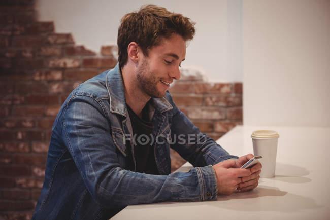 Mann benutzte Handy am Tisch in Café — Stockfoto