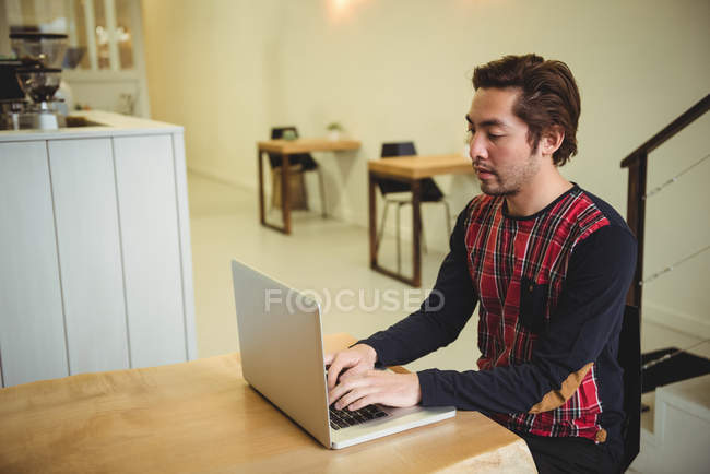 Man using laptop in coffee shop — Stock Photo