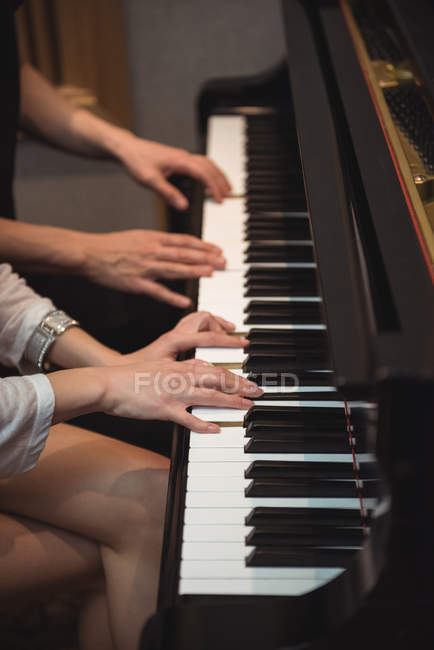 Hands of couple playing a piano in recording studio — Stock Photo