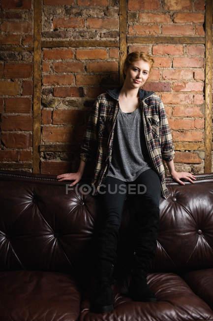 Красива жінка, сидячи на дивані проти цегляна стіна — стокове фото