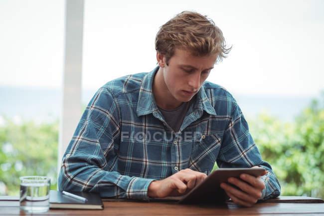 Homme assis au bureau et utilisant une tablette numérique à la maison — Photo de stock
