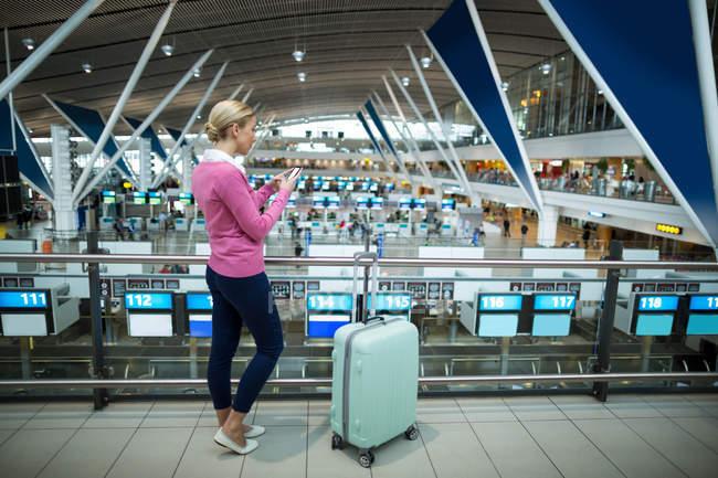 Navetteur féminin avec bagages utilisant un téléphone portable à l'aéroport — Photo de stock
