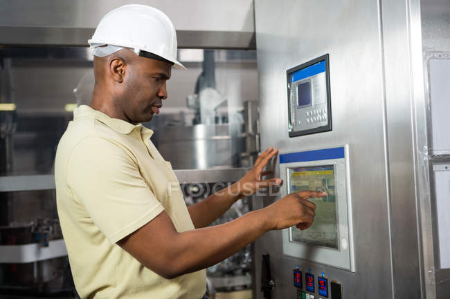 Confident male employee operating machine in manufacturing industry — Stock Photo