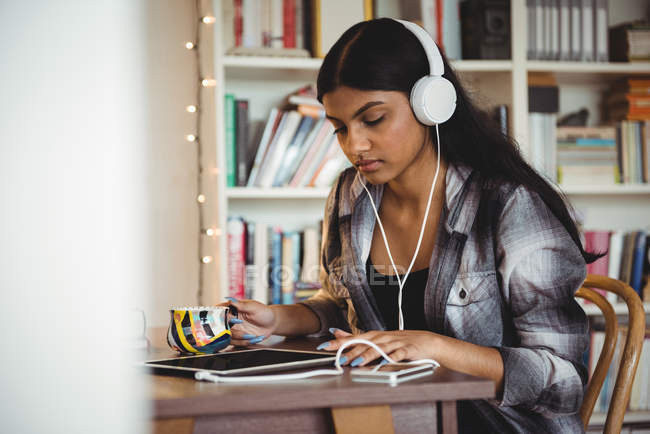Woman listening to music with headphones and digital tablet in living room at home — Stock Photo