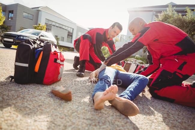 Sanitäter untersuchen verletzte Frau auf Straße — Stockfoto