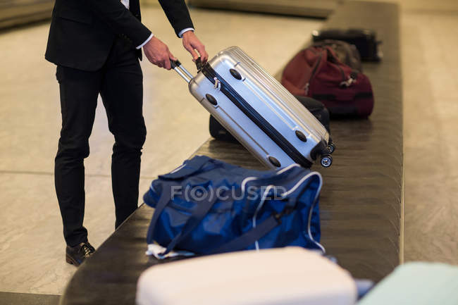 Businessman picking his luggage from baggage claim area at airport — Stock Photo