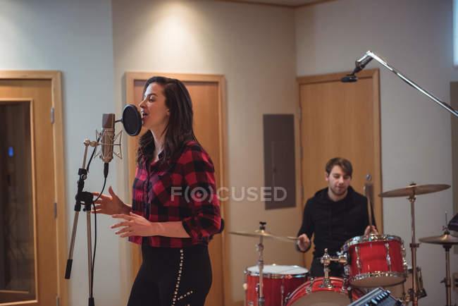 Красивая женщина поет в студии звукозаписи — стоковое фото