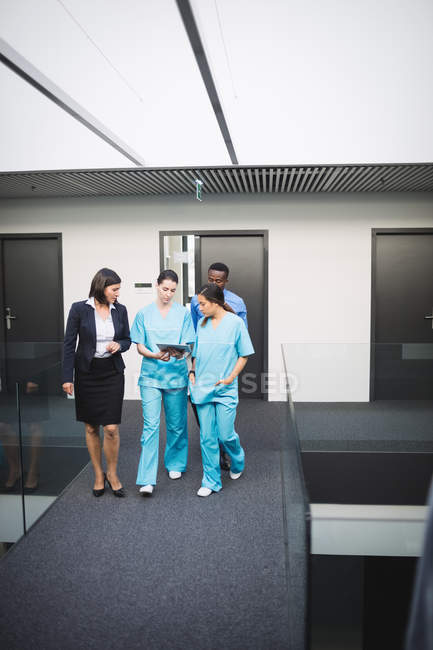 Médico y enfermeras discutiendo sobre tableta digital mientras camina en pasillo de hospital - foto de stock