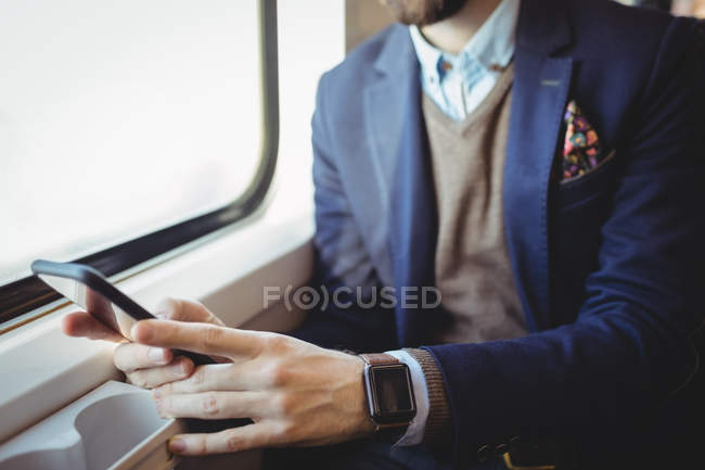 Mid-section of businessman using mobile phone while travelling in train — Stock Photo