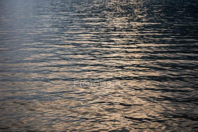 Vista panorámica del agua del río claro con la reflexión de la luz del sol al atardecer - foto de stock