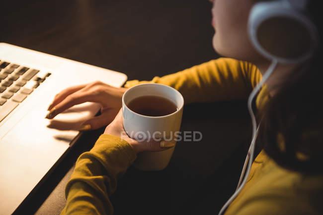 Donna che prende il caffè mentre lavora sul computer portatile nella stanza di studio a casa — Foto stock