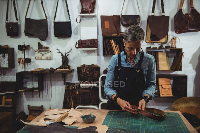 Craftswoman working on a piece of leather in workshop — Stock Photo