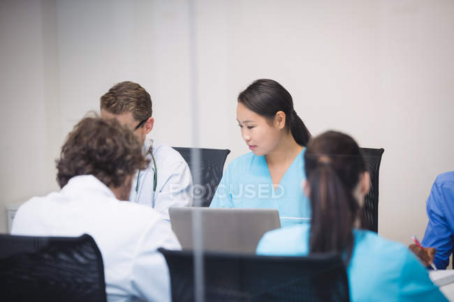 Doctor interacting with colleagues in meeting at conference room — Stock Photo
