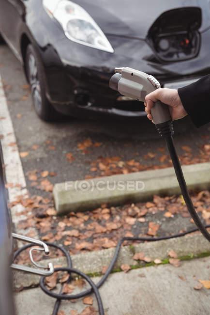 Main de l'homme tenant chargeur de voiture à la station de charge du véhicule électrique — Photo de stock