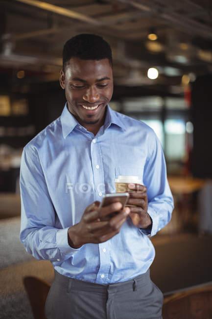 Homme d'affaires détenant la tasse à café jetable et à l'aide de téléphone portable au bureau — Photo de stock