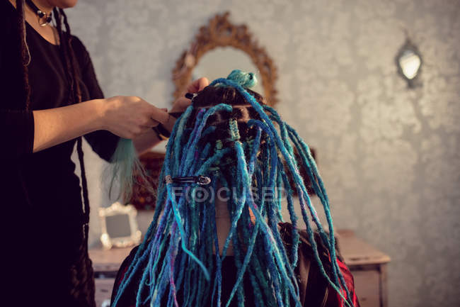 Close-up of beautician styling clients hair in dreadlocks shop — Stock Photo