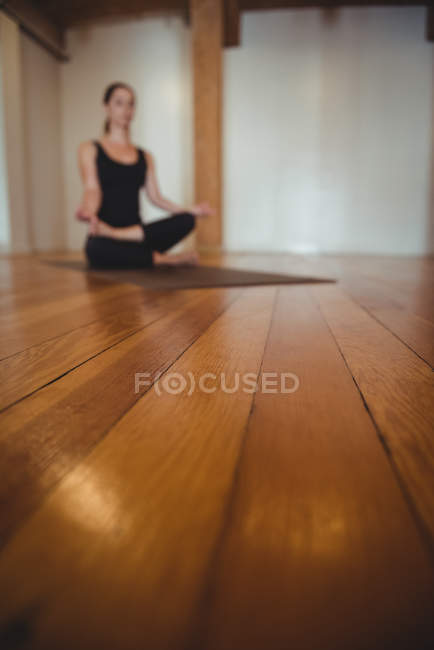 Close-up of wooden flooring in fitness studio with practicing woman in background — Stock Photo
