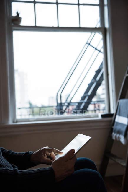 Sección media del hombre usando tableta digital en casa - foto de stock